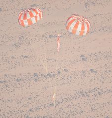 A test article representing the Orion<br /> spacecraft floats to the ground during<br /> the latest Orion parachute test. For<br /> this test, engineers rigged one of the<br /> three red and white main parachutes to<br /> fail, to prove that the vehicle could<br /> land safely with only two working main<br /> parachutes.<br /> Photo credit: NASA